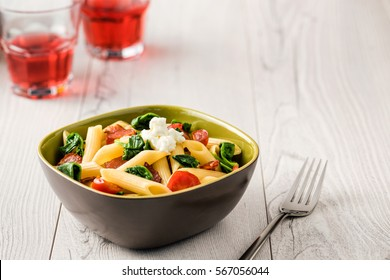 Tomato and Bacon Penne Pasta on white wood table