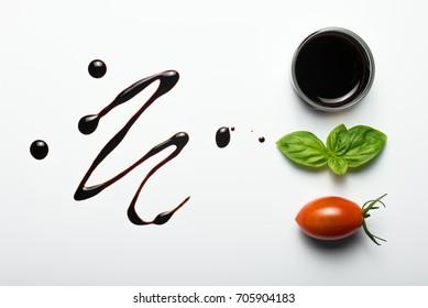 Tomato, basil leaf and balsamic vinegar on white background