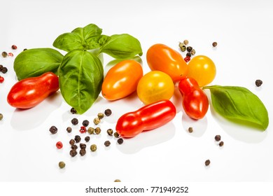 Tomato, basil and pepper isolated on white reflective background