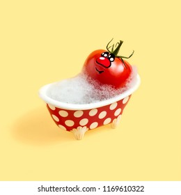 Tomato in bath with soap foam. Concept of food hygiene. Sanitary-hygienic processing of food products. Creative idea, imagination and fantasy. Minimal style