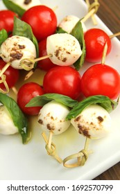 Tomato,  bocconcini and fresh basil on skewer with balsamic and olive oil