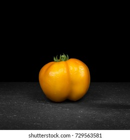 Tomato (breed: Yellow Stuffer) with water droplets on black slate with dark background (solanum lycopersicum)