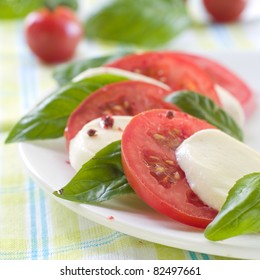 Tomato and cheese appetizer with olive oil and basil. Selective focus