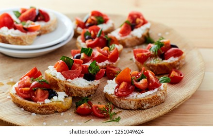 tomato and cheese bruschetta wood dish on table