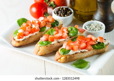 Tomato and cheese fresh made bruschetta. Italian tapas, antipasti with vegetables, herbs and oil on grilled ciabatta and baguette bread. Sandwich.