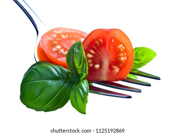 Tomato cherry slices and green basil leaves on a big fork. Macro shot . Healthy vegetarian food.Isolated on a white background.