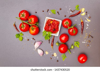 Tomato confiture, jam, chutney, sauce in ceramic bowl. Homemade preservation concept. Fresh tomatoes, dried chili, spices, mustard beans, sea salt. On a stone background, copy space, top view