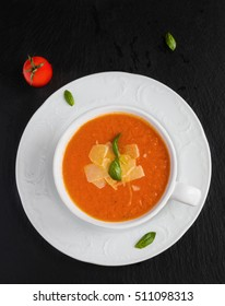 Tomato cream soup with parmesan cheese in white bowl on black stone background. Fresh basil leaves and vegetables, top view.