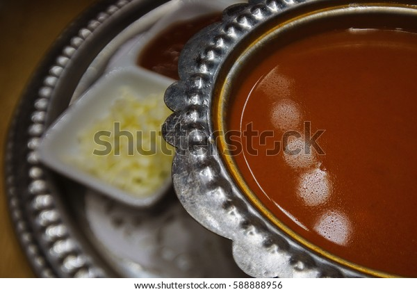 Tomato cream soup in a steel plate on a platter with garnish , the steel dish. Photo Close-up.
