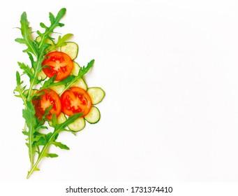 tomate, pepino, hojas de arúgula, borde sobre fondo blanco, vista superior, ramo abstracto