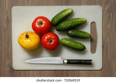 Tomato, cucumber and knife on cutting board.