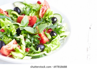 Tomato and cucumber salad with black olives, pomegranate seeds, leek, rocket and fresh thai basil. Home made food. Concept for a tasty and healthy vegetarian meal. Close up. Copy space.
