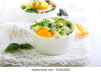 Tomato and egg bake with herbs in ramekins