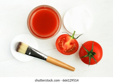 Tomato face mask for natural beauty care. Jar of juicy paste, red fresh fruit, applicator brush, top view white wooden background preparation homemade cosmetic