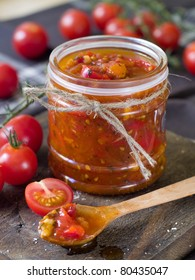 Tomato jam with pepper and garlic in wooden spoon. Selective focus, shallow doff