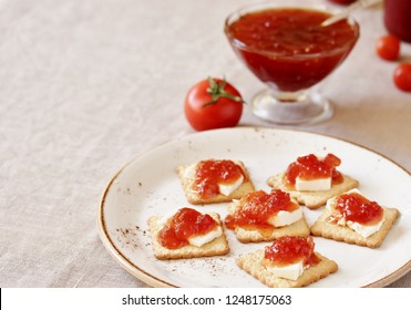 tomato jam with young cheese on a salty cracker appetizer. unusual jam from vegetables. unusual jam.