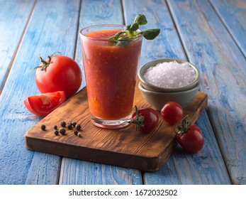 tomato juice in a glass cup on a wooden board.