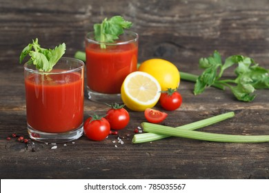 Tomato juice in glasses with celery and lemon on wooden table