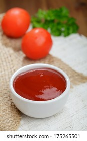 Tomato ketchup in a bowl, fresh tomatoes and parsley