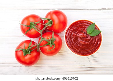 Tomato ketchup sauce in a bowl with basil and tomatoes. Top view