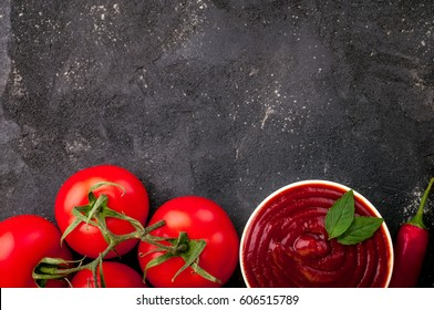 Tomato ketchup sauce in a bowl with chili, basil and tomatoes. Ingredients for cooking  ketchup on dark background. Top view. Copy space