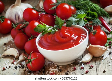 Tomato ketchup sauce with garlic, spices and herbs with cherry tomatoes in a white porcelain bowl on old wooden table, selective focus