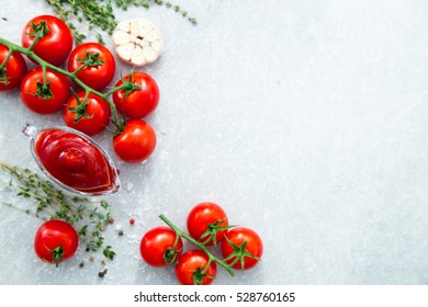 Tomato ketchup sauce with garlic, spices and herbs with cherry tomatoes in a glass bowl on stone table, selective focus. Copy space