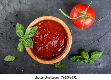 Tomato ketchup sauce in a wood  bowl with  herbs and  tomatoes on dark background, top view