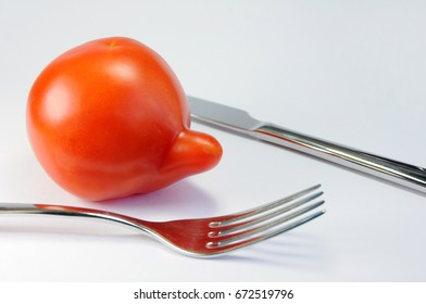 Tomato with knife and fork