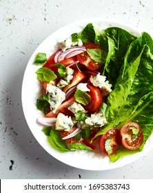 Tomato and lettuce salad with blue cheese, red onion and basil leaves. From top