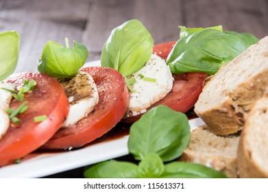 Tomato and Mozzarella Slices on a plate with Balsamic Vinegar