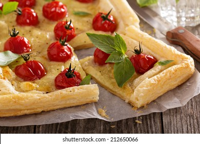 Tomato and mozzarella tart with basil on puff pastry