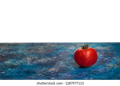 Tomato on the countertop and place for text. Fresh ripe tomato lying on a colorful blue background.