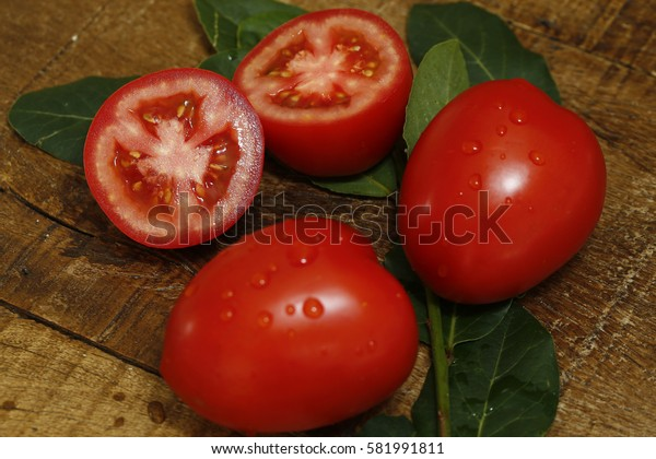 Tomato, one of several Aztec contributions to world cuisine, on wooden background