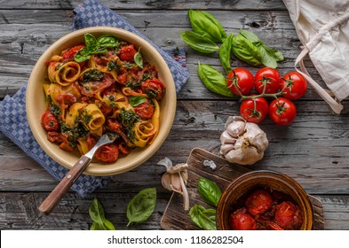 Tomato pasta basil on wood vintage board, fresh herbs and cheese in