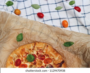 Tomato pie with fresh basil on a baking paper, pie on a cloth. Cherry tomato mix pie with cheese. Top view.