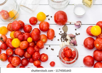 Tomato prepared for preservation and empty glass jars on a white wooden background with seasonings near .Top view