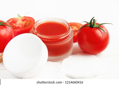Tomato pulp face mask in jar, fresh red plant, white table. Juicy vitamin rich skin care at home spa.