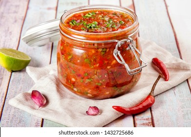 Tomato salsa in a glass jar. Homemade spicy tomato sauce with chilli, garlic and lime. Close up and horizontal orientation.