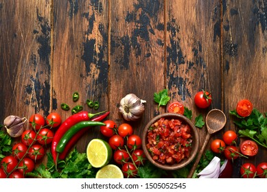 Tomato salsa (salsa roja) - traditional mexican sauce  with ingredients for making on a wooden background.Top view with copy space.