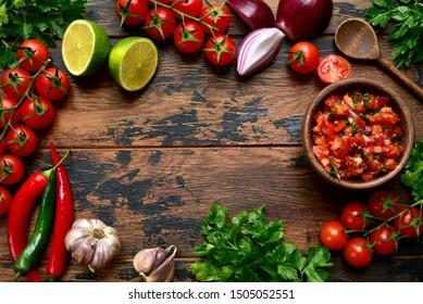 Salsa de tomate (salsa roja) - sauce mexicaine traditionnelle avec ingrédients pour la fabrication sur fond bois.Vue de dessus avec espace pour copie.