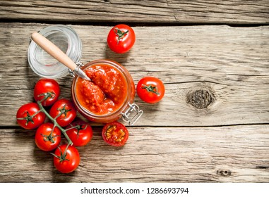 Tomato sauce in a glass jar with fresh tomatoes. On a wooden background.