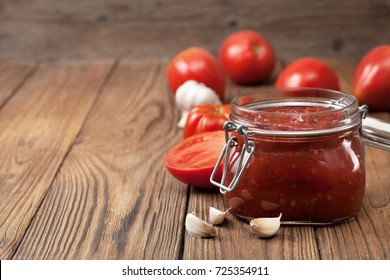tomato sauce in a glass jar, fresh tomato, parsley and spices on a wooden background