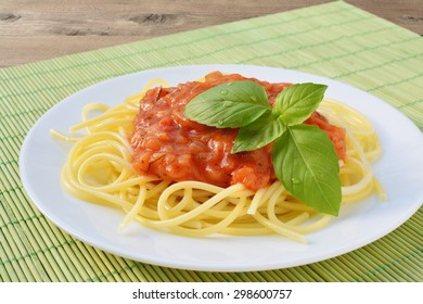 Tomato sauce with spaghetti and herbs on white plate.