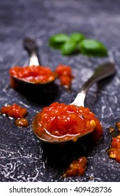 Tomato sauce in the spoon on a dark surface. Selective focus.