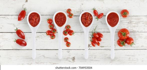 Tomatensoßlöffel mit Tomaten und Basilikum einzeln auf weißem Holzhintergrund
