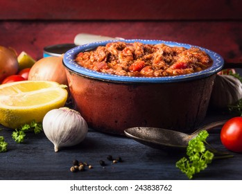 tomato sauce with tuna fish in old pot with spoon and spices