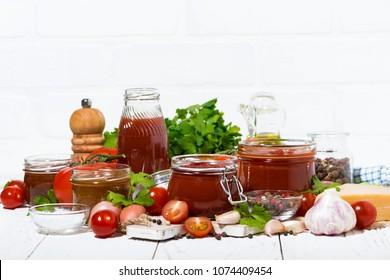 tomato sauces, pasta and fresh ingredients on white wooden table, horizontal