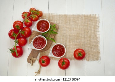 Tomato sauce.tomato ketchup.The recipe for ketchup. home made sauce ketchup in white plates, ripe red tomatoes and burlap on a white wooden board background