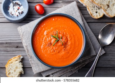 Tomato soup in a black bowl on wooden background. Top view. Copy space